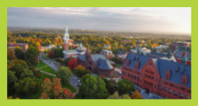 Aerial view of green and orange trees throughout campus filled with red stone building and white tower in the distance.