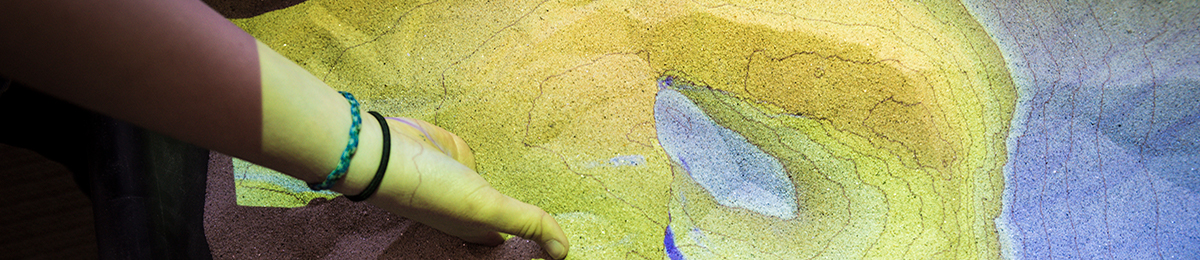 Image of someone digging into an augmented reality sandbox created by Rachel Seger '16.