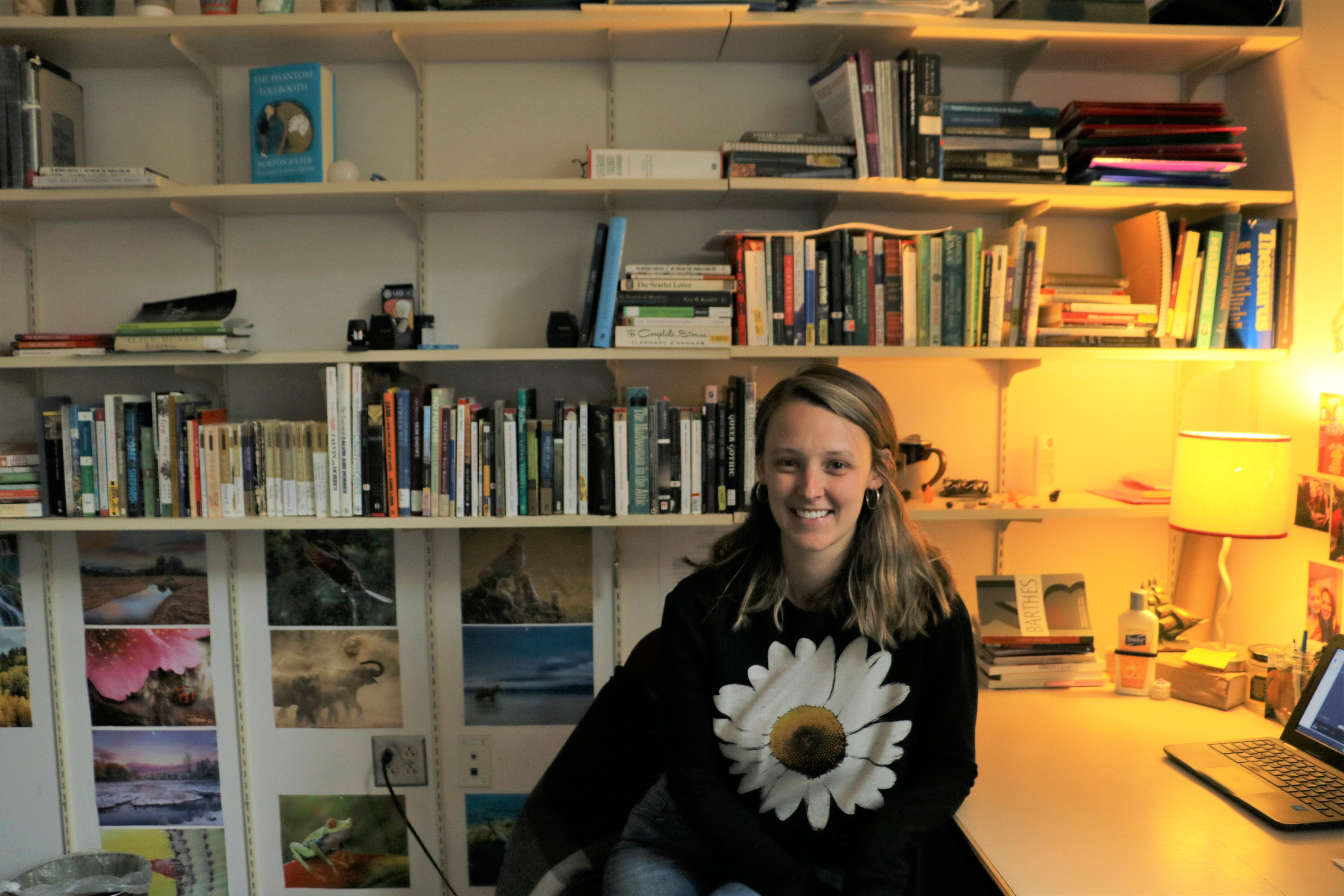 Casey O'Reilly, shoulder length light brown hair, smiling at the camera and sitting at her desk in front of a bookcase