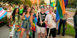 Students hold rainbow and trans flags at UVM Convocation