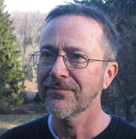 David Lloyd, looking off camera to the left, dark gray hair and salt and pepper short beard, wearing thin dark rimmed glasses and a black shirt