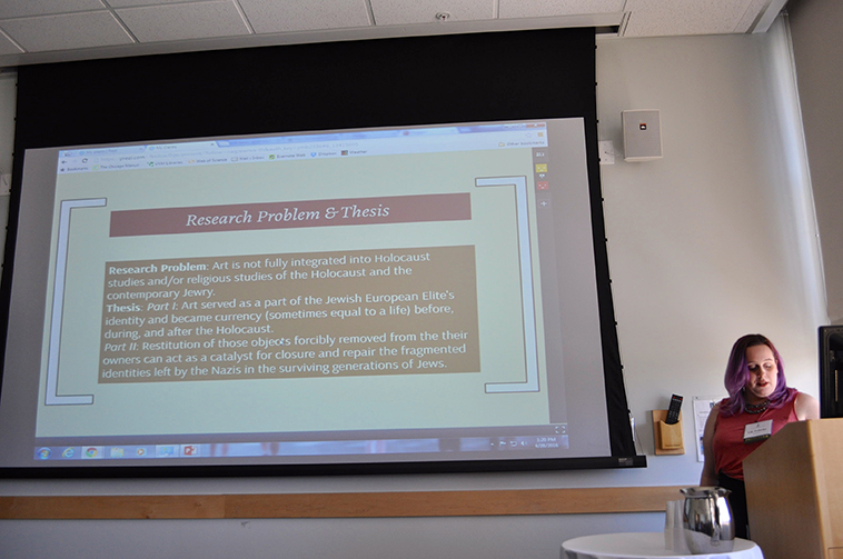 Photo of a 2016 Student Research Conference oral presentation consisting of a presenter behind a podium and a presentation on a projector screen.