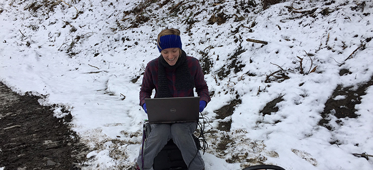 Hannah '18 using her computer out in the snow while collecting data.