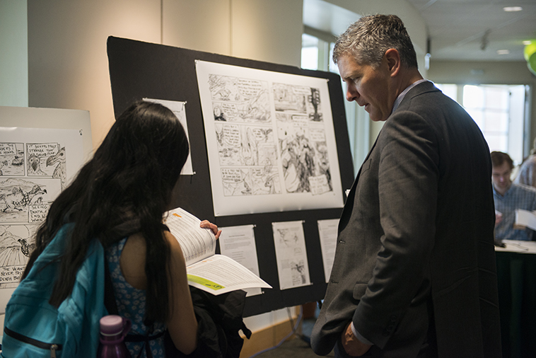 Photo of the Dean of the Honors College talking with student in front of a creative presentation of graphic novel at the 2017 SRC.