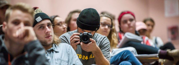 Banner for minor in Reporting and Documentary Storytelling. Student wearing a black beanie sitting at a desk holding a camera pointed at the camera