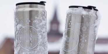 two silver coffee cans with the UVM tower steeple in the background