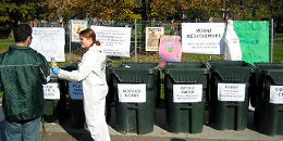 student eco-reps sort recycling in front of a row of trash cans
