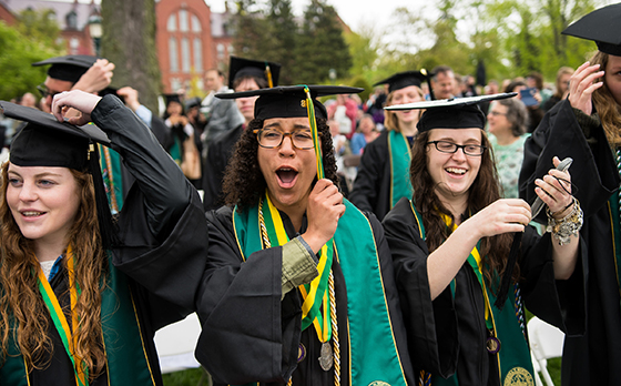 Students in caps and gowns cheer and turn their tassels at the 2018 UVM Commencement Ceremony