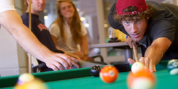 A student lines up a shot in a game of pool while another student watches