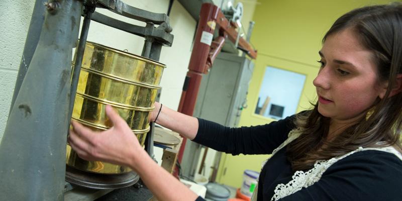 Karine Manuelson working on a machine in a lab