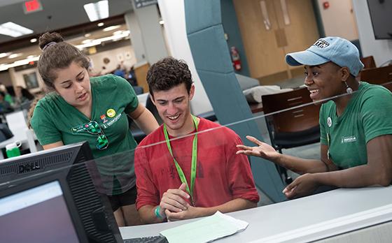 Three students gather around a computer