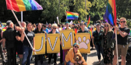 Students, staff and faculty posing with rainbow flags and sign that says UVM at Burlington Pride Parade