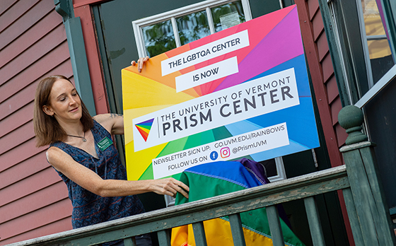 A woman holds a sign displaying the name, The University of Vermont Prism Center
