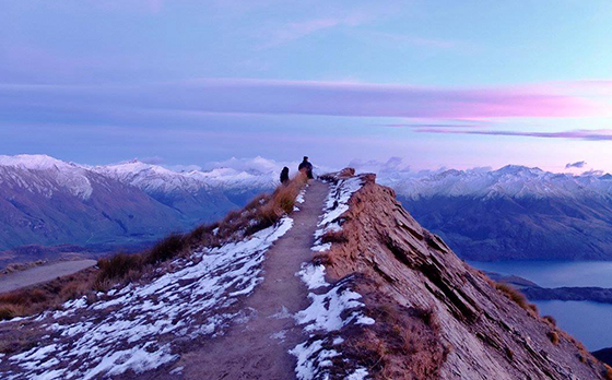People stand atop Roy's Peak in Wanaka, New Zealand at sunrise