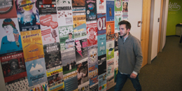 a student walks by a wall of posters in the department of student life