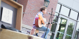 man playing a guitar on an outdoor stage