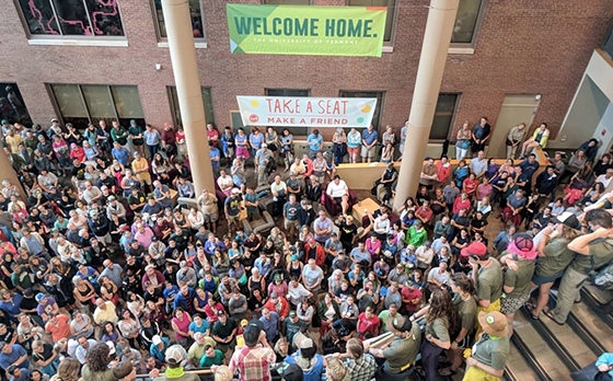 Hundreds of students gather in the lobby of the Davis Center under a banner that reads, Welcome Home.