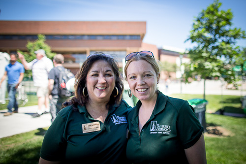 two uvm women staff in green polos