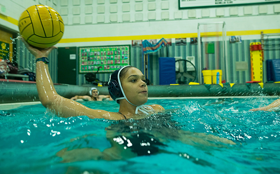 A student athlete in pool plays water polo