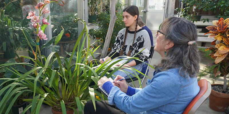 two women drawing a flower in a greenhouse