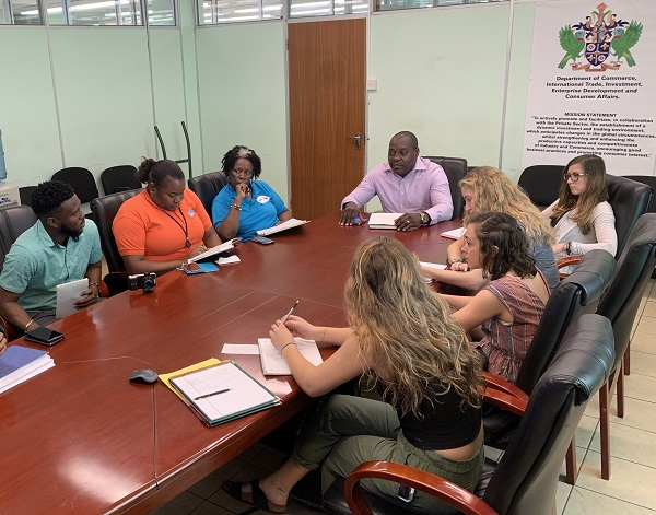 Students meeting with St. Lucian representatives at a table