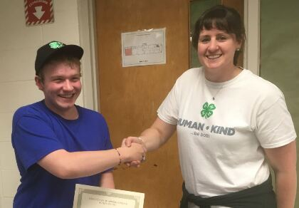 Andrew Dutil shaking hands with a 4-H representitive