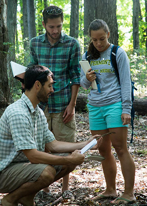 Ashley Eaton and classmate learn in the woods with Matthew Kolan.