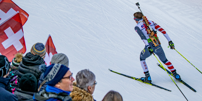Biathlete skis past spectators