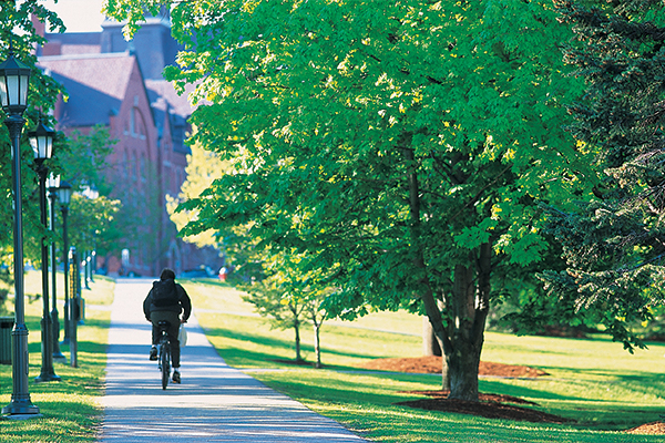 A student bikes along a path on UVM's campus