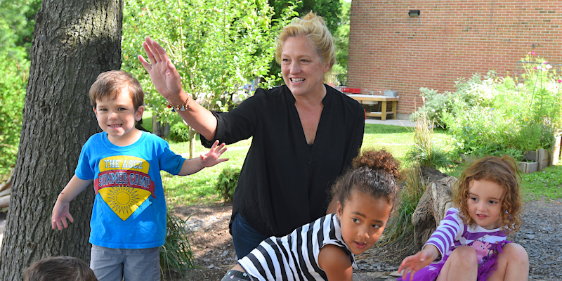 Barbara outside on playground with kids at UVM Campus Children's School