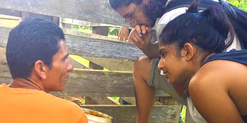 Two students learn from local farmer