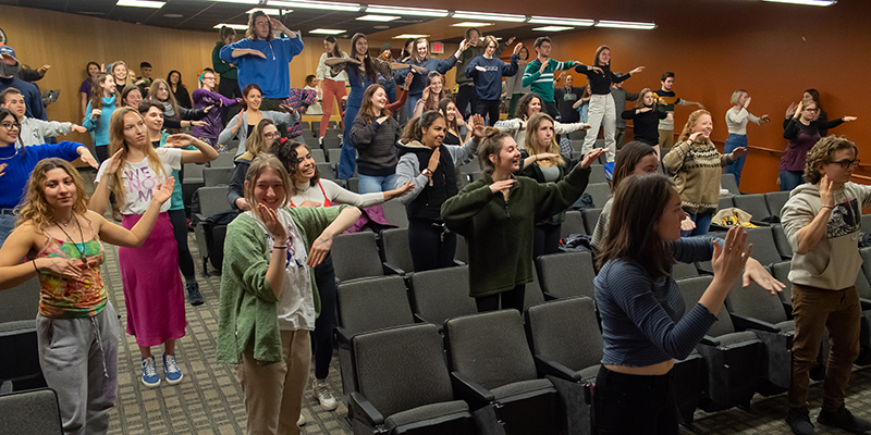 Students in a lecture hall follow along in a sequence of dance moves led by professor Paul Besaw.