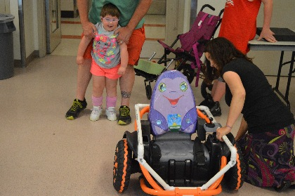Miley walks with her father's help toward her adapted Power Wheels Wild Thing