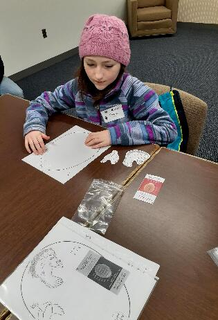 A female student studies the life cycle of a chicken through paper worksheets.