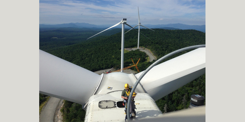 Worker on top of wind turbine at wind power site
