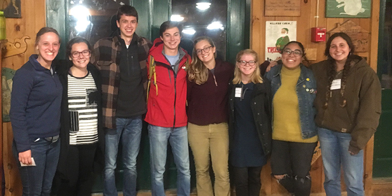 Eight students stand in the Hulbert Outdoor Center in Fairlee, Vermont.