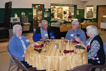 Long time volunteers of 4-H gathered around eating dinner.