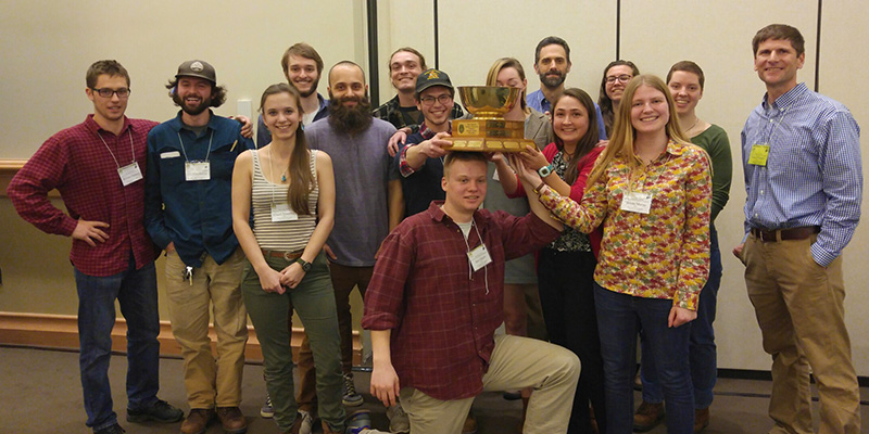 Group of students and faculty displaying Quiz Bowl trophy