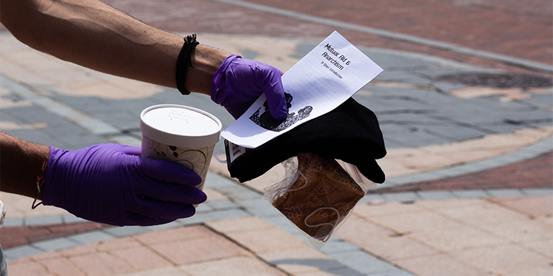 Sam Bliss, wearing disposable gloves, holds out a food container and pamphlet.