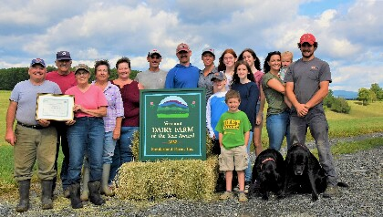 The Sunderland family stands in front of their dairy farm sign