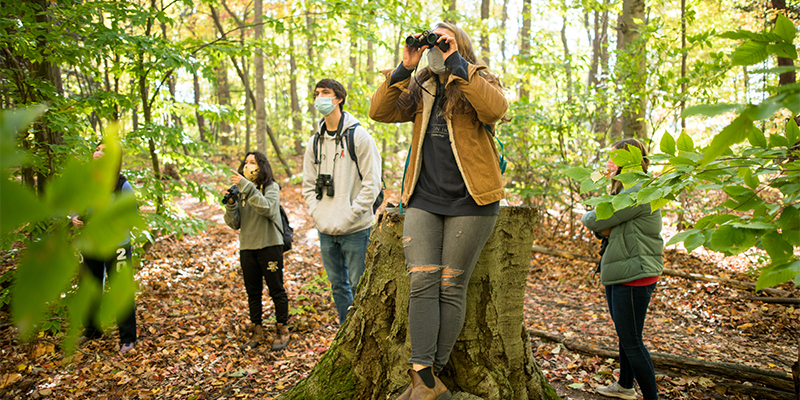 Four college students with face masks and binoculars in the woods