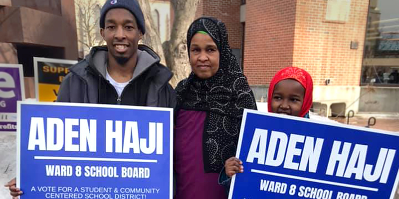 Aden Haji holds his campaign signs with his mother and sister.