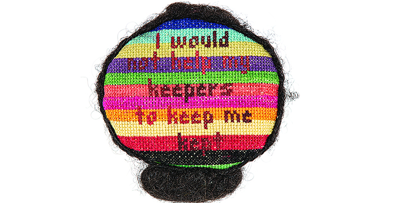 "round embroidered sculpture, rainbow background, with the words ""I would not help my keepers to keep me kept."" on top"