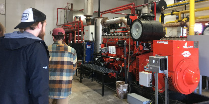 Students explore the power generator continuously fed by biogas generated by the digester at a Vermont farm