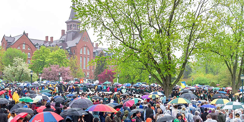 A sea of umbrellas on the UVM green in front of Old Mill