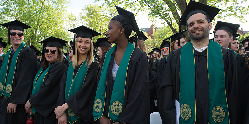 graduates stand on the UVM Green