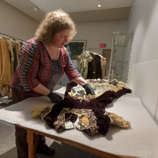 Conservator Sarah Stevens examines a Victorian dress