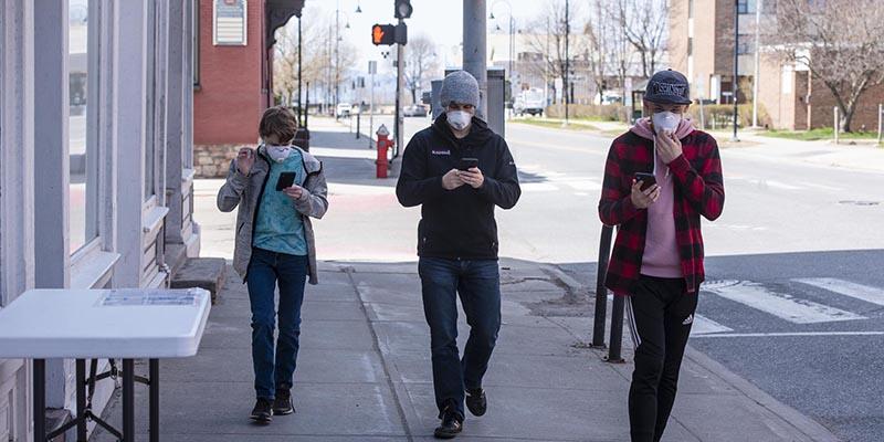 Three people walking down a Burlington street wearing face masks.