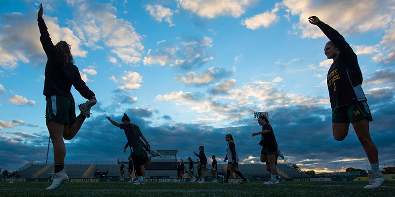 Women's lacrosse warms up at Virtue Field at dawn
