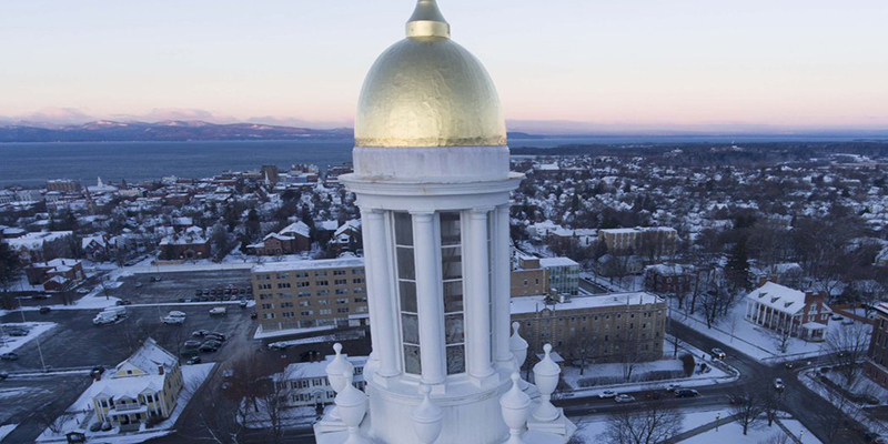 The dome of Ira Allen with Burlington in distance via drone